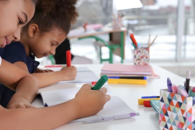 Leuke afro-amerikaanse meisjes tekenen op les