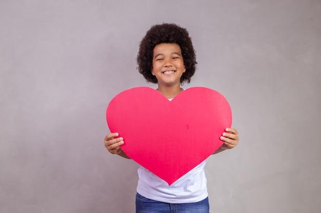 Leuke afrojongen die een grote hartkaart met ruimte voor tekst houdt.