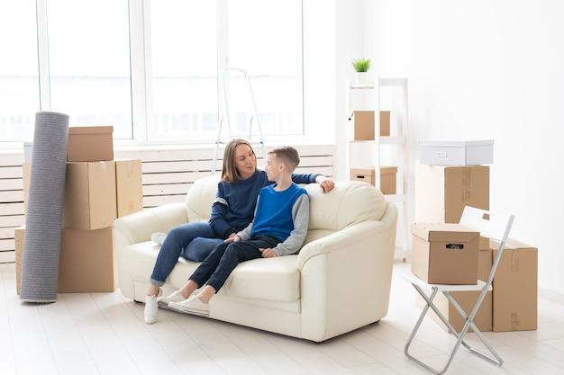 Leuke alleenstaande moeder en zoontje ontspannen na de verhuizing. het concept van housewarming hypotheek en de vreugde van nieuwe huisvesting.