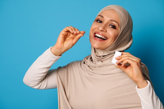 Leuke arabische vrouw met bedekt hoofd en perfecte glimlach met behulp van een tandzijde en poseren