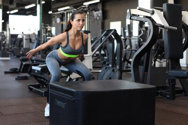 Leuke atletische brunette die springoefeningen doet in een cross-training gym.