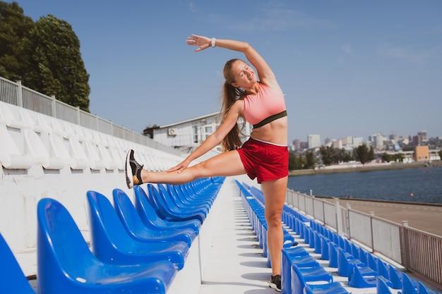 Leuke atletische vrouw met lang haar die zich uitstrekt voordat ze in het stadion jogt