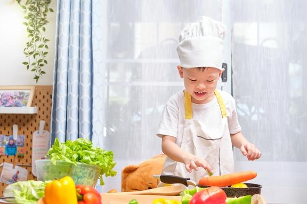 Leuke aziaat weinig jongenskind chef-kokhoed dragen en schort die pret voorbereidingen treffen, die gezond voedsel in keuken koken