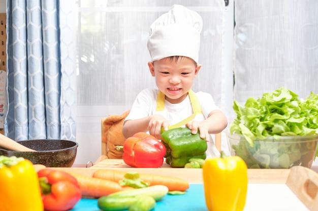 Leuke aziaat weinig jongenskind die chef-kokhoed en schort dragen die pret hebben die voorbereidingen treffen, gezond voedsel in keuken koken, leuke binnenactiviteiten voor kleuterschoolkinderen