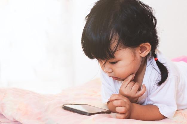 Leuke aziatische babymeisje het spelen smartphone liggend op haar bed in haar ruimte