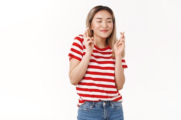 Leuke aziatische blonde vrouwelijke student hoopt alle examens te halen en wensen te doen dichte ogen glimlachen dromerige kruis vingers veel geluk anticiperen op positieve resultaten hopelijk bidden droom die uitkomt witte muur