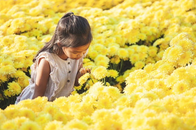 Leuke aziatische de liefdebloem van het kindmeisje en het hebben van pret met mooie bloem in de bloementuin