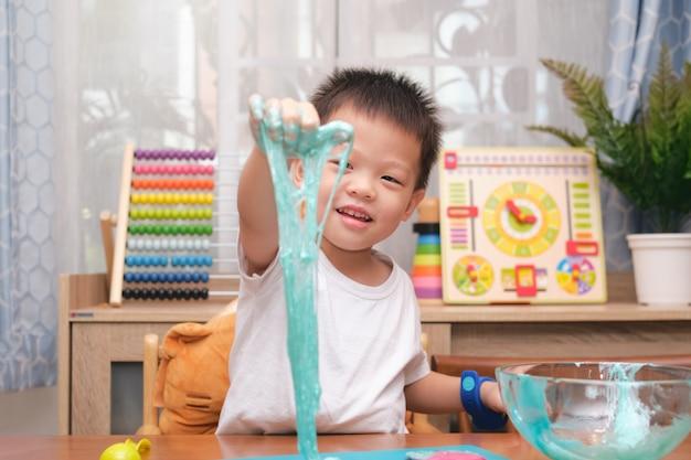 Leuke aziatische jongen die pret heeft die slijm maakt