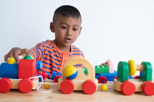 Leuke aziatische jongen speelgoed spelen in de kamer