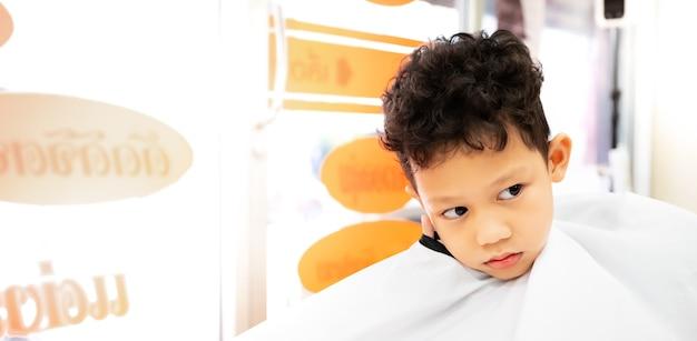 Leuke aziatische kindjongen die haar krijgt dat door kapper bij kapsalon wordt geknipt. haarverzorging en jeugd lifestyle concept.