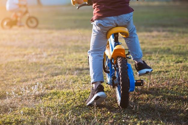 Leuke aziatische kindjongen die pret heeft om een fiets in het park te berijden