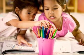 Leuke aziatische kleine meisjes tekenen met hun kleurpotloden. vintage kleurtoon