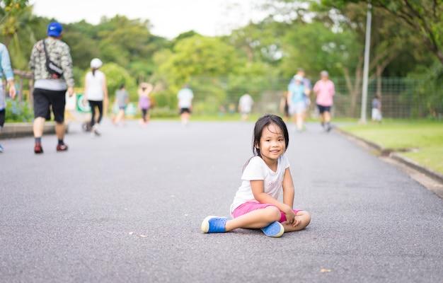 Leuke aziatische liittemeisjeszitting op straat in het park