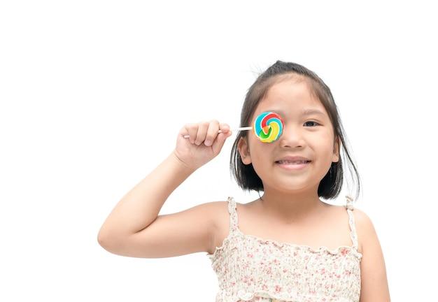 Leuke aziatische meisjeglimlach met suikergoed dat op witte achtergrond wordt geïsoleerd