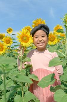 Leuke aziatische meisjeglimlach met zonnebloembloem