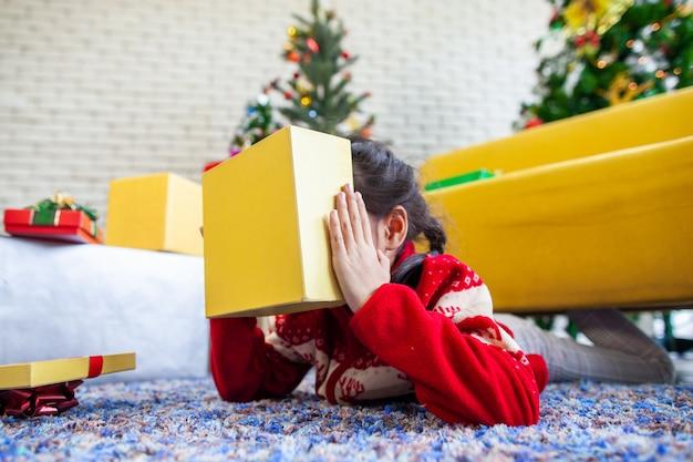 Leuke aziatische meisjesverrassing met gift en het houden van mooie giftdoos bij kerstmisviering in hand