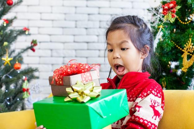 Leuke aziatische meisjesverrassing met gift en het houden van mooie giftdozen bij kerstmisviering in hand