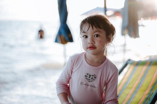 Leuke aziatische meisjeszitting op het strand met een zonnige dag.