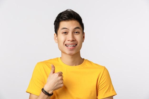 Leuke aziatische mens in gele t-shirt die duim opgeeft