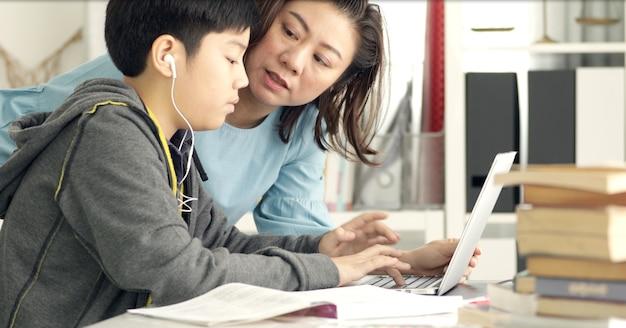 Leuke aziatische moeder die uw zoon helpt die uw thuiswerk doet.