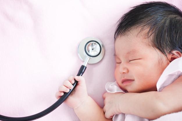 Leuke aziatische pasgeboren babymeisje die en medische stethoscoop in hand slapen houden