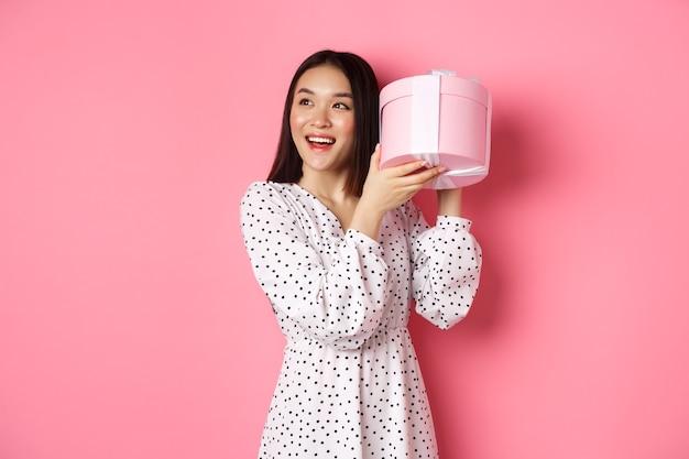 Leuke aziatische vrouw die doos met cadeau schudt, glimlachend en geïntrigeerd kijkt, raad eens wat erin aanwezig is, staande over roze