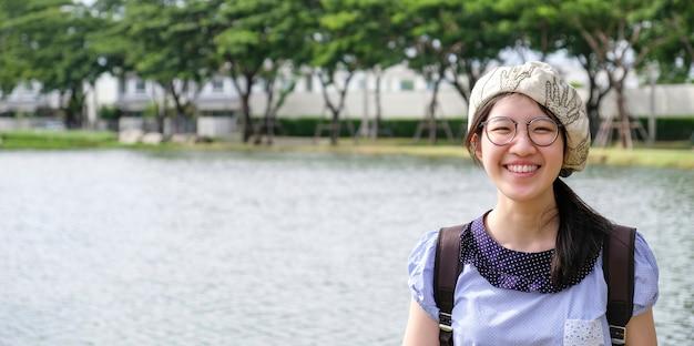 Leuke aziatische vrouw die glazen draagt die in de tuin glimlachen
