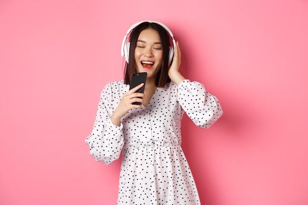Leuke aziatische vrouw die karaoke-app speelt, in mobiele telefoon zingt en een koptelefoon gebruikt, in jurk over roze achtergrond staat