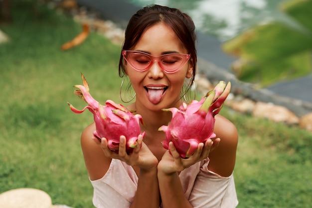 Leuke aziatische vrouw die tong toont, grimassen maakt en roze draakvruchten in handen houdt.