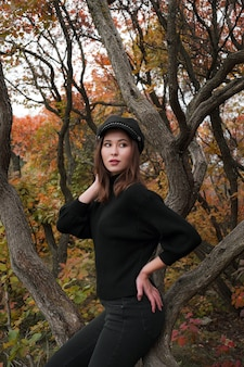 Leuke aziatische vrouw in een goed humeur poseert in de herfstdag, genietend van het goede weer. de kunst van het werk van een romantische vrouw. vrij zacht model kijkt naar de camera.