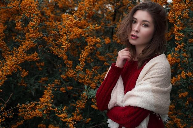 Leuke aziatische vrouw in een goed humeur vormt in de herfstdag, genietend van het goede weer. de kunst van het werk van een romantische vrouw