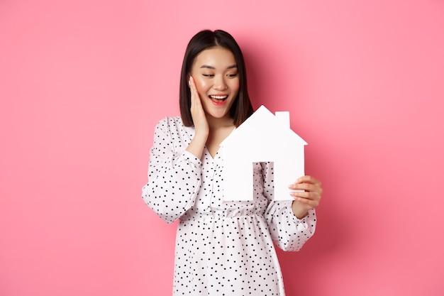 Leuke aziatische vrouw in onroerend goed op zoek naar appartement die gelukkig kijkt naar papieren huismodel dat tegenover elkaar staat ...