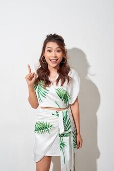 Leuke aziatische vrouw in tropische print groene jurk denken en verbeelding op witte achtergrond