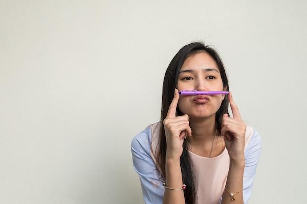 Leuke aziatische vrouw op witte muurachtergrond