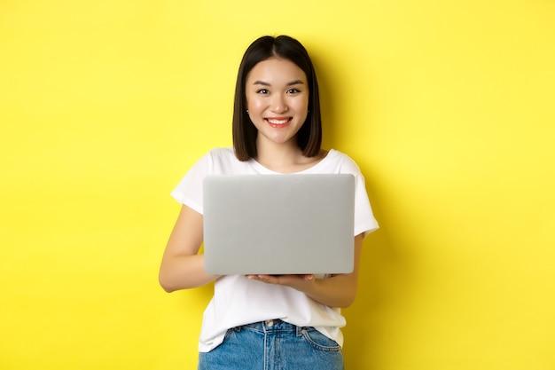 Leuke aziatische vrouw studeren op laptop en glimlachen, staande in wit t-shirt en jeans tegen gele achtergrond.