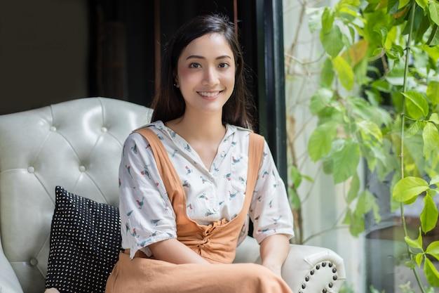 Leuke aziatische vrouw zit op de bank of stoel en kijkt naar de camera en lacht gelukkig in portretten thuis tijdens ontspannen tijd.