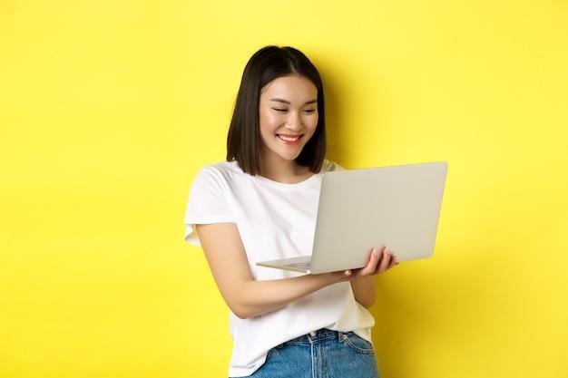 Leuke aziatische vrouwelijke student die aan laptop werkt, het scherm leest en glimlacht, gele achtergrond.