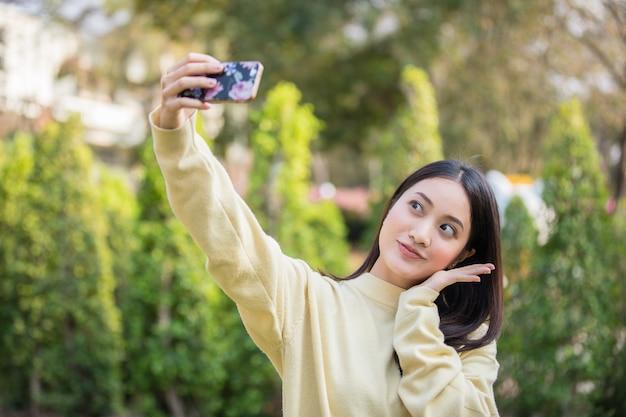 Leuke aziatische vrouwen gebruiken hun telefoons om selfies te maken en gelukkig in de tuin te glimlachen.
