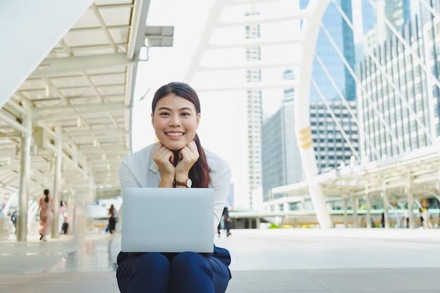 Leuke aziatische vrouwenzitting op vloer met laptop met het glimlachen.