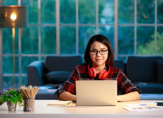 Leuke aziatische zakenvrouw die thuis werkt in de woonkamer met schemerhemel op de achtergrond van het huis. ze werkt met een laptop-notebookcomputer en kijkt naar de camera.