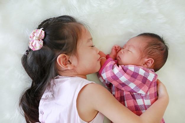 Leuke aziatische zuster die slaap pasgeboren baby omhelst die op witte bontachtergrond ligt.