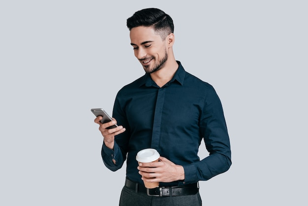 Leuke babbel. knappe jonge man die een smartphone vasthoudt en ernaar kijkt met een glimlach
