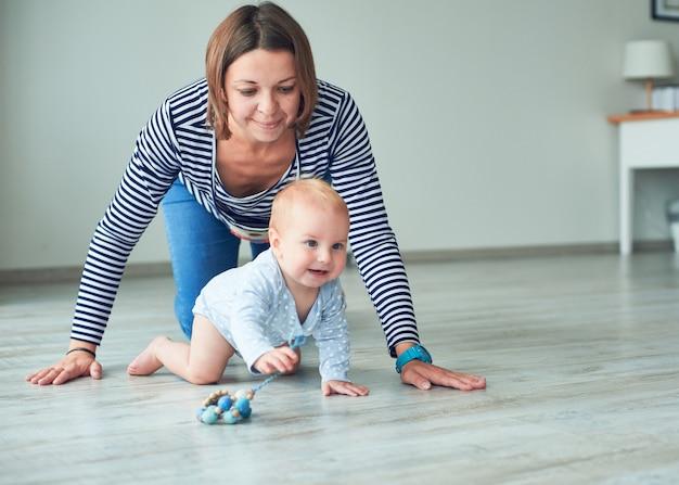 Leuke baby en jonge moeder die thuis kruipen
