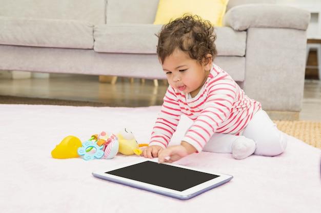 Leuke baby op het tapijt met tablet thuis