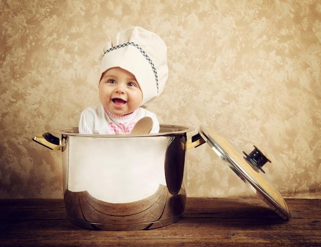 Leuke babychef-kok in een enorme ketel