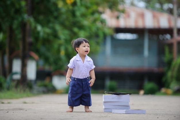 Leuke babyjongen die in openlucht, babykind na school ontspannen.