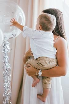 Leuke babyjongen die transparante ballon bekijkt. thuis vierend kinderen verjaardag in helder binnenland met zijn moeder