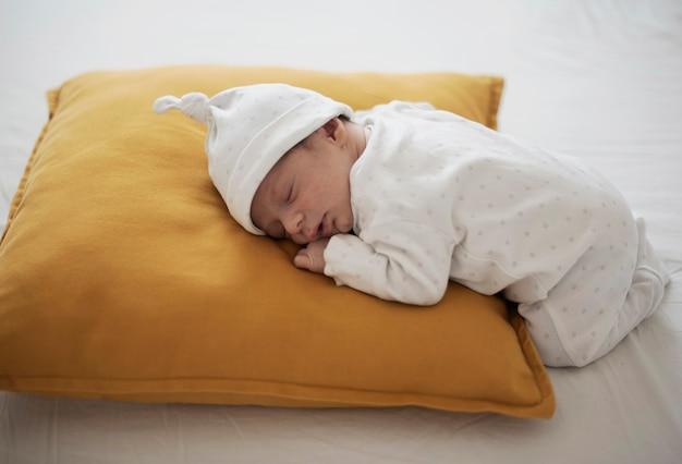 Leuke babyslaap op een geel hoofdkussen