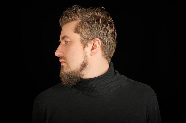 Leuke bebaarde man, half gezicht portret, zwarte achtergrond. jonge kerel in zwarte polohals trui. zelfverzekerde, succesvolle man.