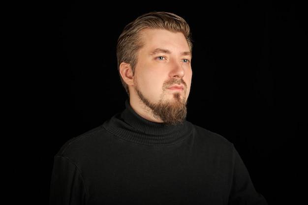 Leuke bebaarde man, half profiel portret, zwarte achtergrond. jonge kerel in zwarte polohals trui. zelfverzekerde, succesvolle man.